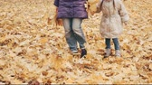 Happy little girl with her mother kicking autumn leaves in the park.