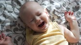 Little boy laughing while lying on the back