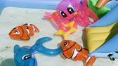 Pool with inflatable toys. Dolphin, fish and octopus