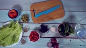 4k, Preparing fresh vegetable salad with greek cheese. Food stop motion animation. Top view on gray kitchen counter.