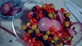 fliege : slow motion, fresh blue onion falling into tho bowl salad tomato, cucumber, olives drops on kitchen healthy, close up, macro, HD