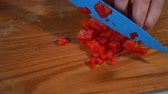 Extreme close up view of female hand chopping juicy red pepper on a wooden chopping board.Greek salad, Cooking a dish, European cuisine, being a gourmet. HD