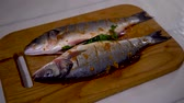 4K, Cooking of three sea bass on white table. Cook preparing fresh fish for baking.