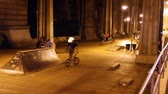 patim : Youth riding bikes in an urban skatepark in New York at night. Includes subtle blurring of faceslogos
