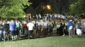 parkosított : Time lapse of a crowd of teenagers socializing in a park at night.