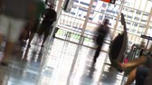 motion blur : Canted time lapse shot of travelers with luggage, walking down an airport corridor