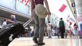 chodba : Low angle of crowds of people walking down the terminal of an airport, with audio