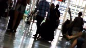 verificar : Canted shot of people with luggage, walking down the check-in hall of an airport.