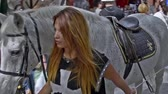 hafta : ALCALA DE HENARES, SPAIN - OCTOBER 8th 2016: Beautiful blonde woman walking by the streets of Alcala de Henares city, with Don Quixotes horse and Sancho Panzas donkey, on October 8th 2016. Cervantinos market. Stok Video