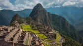 citadel : Picturesque timelapse view of famous ruins of ancient Inca city of Machu Picchu in Peru, with vivid green grass and steep Huayna Picchu mountain in background