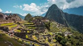 citadel : Timelapse of ancient Inca city Machu Picchu and Huayna Picchu mountains in background, under cloudy sky Stock Footage