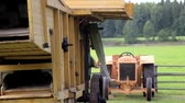 front end loader : A very up close image of the straw hammer mill working and processing the products making the farm chores finish fast. Close up of the working old antique straw hammer mill tractor  Stock Footage