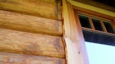 ageless : Cabin log house wall and its wooden glass window. The cabin log house logs wall is brown in color and has a nice glass window design.  Stock Footage