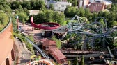 eğlence peşinde : Overhead view of fun rides. Several thrill rides can be seen overhead and some big buildings from afar. The aerial view of the amusement park seeing all the fun rides.