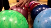 bowling alley : Upclose image of bowling ball and lady arranging the balls looking for the right weight she can use to play.  Stock Footage