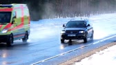 asphalt : Two cars simultaneously running fast on the road with thick snow and pine trees on the roadside