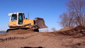 raspador : A yellow bulldozer moving the brown soil on the construction site Stock Footage