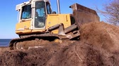 raspador : A heavy bulldozer moving some soil on the ground and going back and forth Stock Footage