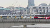 The subway trains and the bridge in London. Shown are the runnin train and the buses and cars passing along the bridge