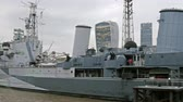 Seen is the very huge white warship called Belfast. It is docked on the Thames river where lots of tall buildings in the background
