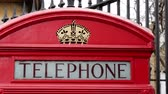 esculpida : The telephone booth on the front of a black gate. With a royal crown carved on top it is one of the many red telephone booths in London