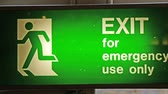 men : A green Exit sign for emergency use only. This is installed on the side of the building
