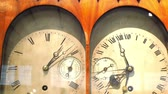 time : Two old clocks inside a clock cabinet. They have a differnt style of clock and has Roman Numerals in numbers Stock Footage