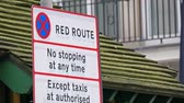 No Red Route sign on the street of London. It means no stopping anytime on that area