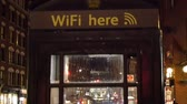 A Wifi here sign on a telephone booth. It means you can use wifi or free internet access on that area