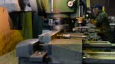 A man at work on a vertical milling machine. Machining of a metal part on a metal-cutting machine.