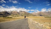 zanskar : Smart Asian woman covered her face walking on lonely road in sunny day, Padum, Zanskar valley, India