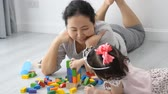 cúbico : Asian girl and her mother playing wooden colour blocks at home