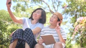 Asian mother and son sitting in the park outdoor and selfie with smartphone together, family lifestyle concept Стоковые видеозаписи