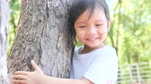 clams : Asian girl hugging tree, slow motion.