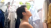 drying rack : Back of boy looking clothes hanging at home, lifestyle concept. Stock Footage