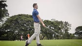 cursos : Golfer hitting ball on green grass, slow motion