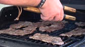 přídatný : Mans hands cooking meat on grill