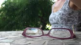 alcance : Woman putting on reading glasses Stock Footage