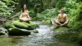 young couple doing yoga by the river