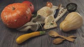 abóbora : Composition from Halloween vegetables. Wooden table background decorated with orange and yellow pumpkins, onion, seeds, squash, fresh bread, wooden spoons and knife with a glare of light on it. 4K.