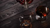 alkoholik : Luxury brandy. Hand takes round bottle and pours golden cognac in one of two glasses on wooden table. Brandy, cognac, snifter, binge. Slow motion. 4K.