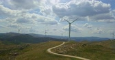 windturbines : Aerial view, by drone of a wind turbines on top of mountains, cloudy sky as background, in Portugal Stockvideo