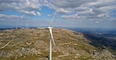 energia alternativa : Aerial view, by drone of a wind turbines on top of mountains, cloudy sky as background, in Portugal Stock Footage