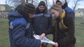 poça de água : Taman, Russia - February 27, 2018: Planning the planting of young trees by workers in the park. The engineer gives instructions to the workers.