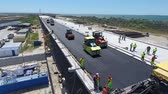 reconstruction : Construction of the road and paving of asphalt during the construction of the bridge. Large-scale construction of infrastructure. Stock Footage