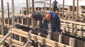paver : Taman, Russia - May 20, 2017: Workers mount the formwork of a reinforced concrete structure.