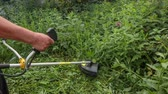 A man mows the grass with a trimmer Dostupné videozáznamy
