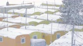 домик : snowy town of yellow prefabricated lodges for construction workers and watchmen amidst trees in Yamal in Russia