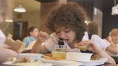 soupon : KAZAN, TATARSTAN  RUSSIA - JANUARY 20, 2017: Slow motion nice curly-haired schoolgirl in uniform eats soup with bread at spacious bright school canteen on January 20 in Kazan