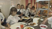 purê : KAZAN, TATARSTAN  RUSSIA - JANUARY 20 2017: Wideshot girl in school cafeteria take plate of food and put it on her tray on January 20 in Kazan